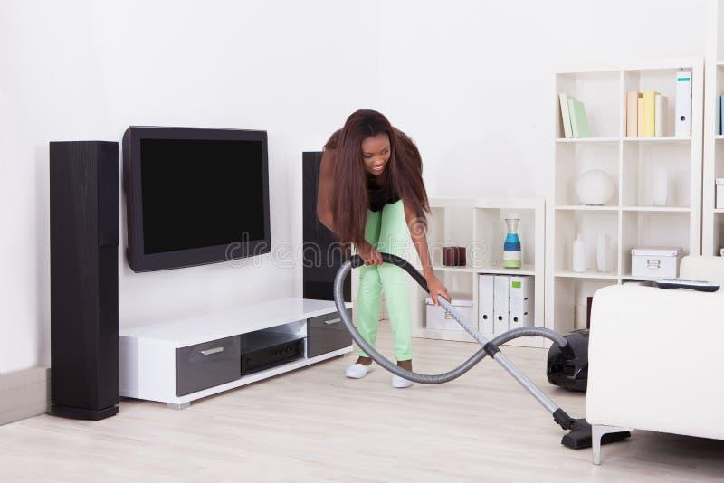 Καθαρίζοντας σπίτι γυναικών με την ηλεκτρική σκούπα στοκ φωτογραφία με δικαίωμα ελεύθερης χρήσης