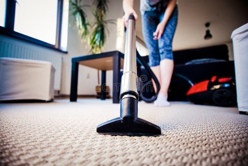 καθαρίζοντας τάπητας γυναικών με μια ηλεκτρική σκούπα στο δωμάτιο - εστιάστε στο χ στοκ εικόνα