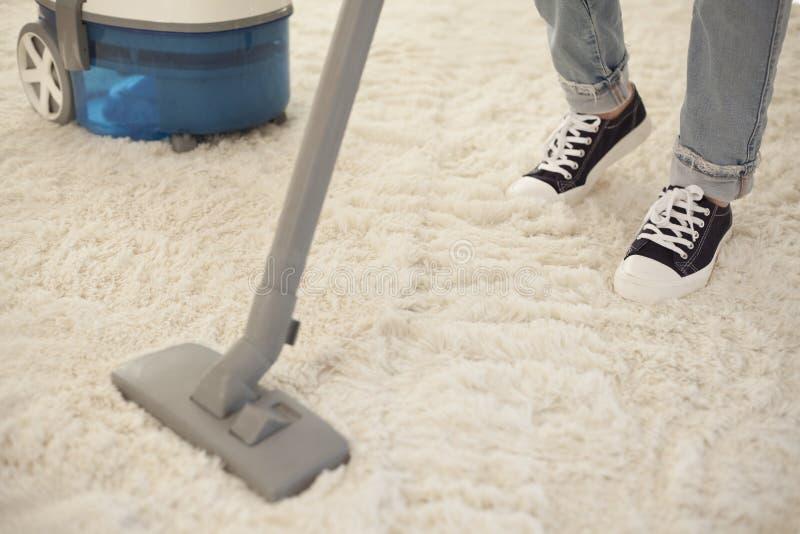 Καθαρίζοντας τάπητας γυναικών με μια ηλεκτρική σκούπα στο δωμάτιο στοκ εικόνες