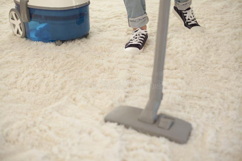 Καθαρίζοντας τάπητας γυναικών με μια ηλεκτρική σκούπα στο δωμάτιο στοκ εικόνα