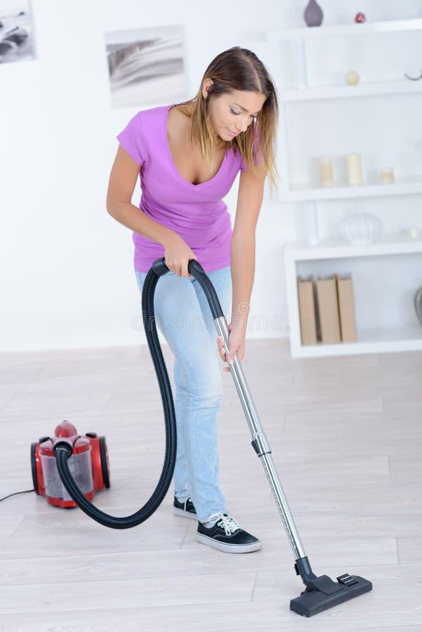 Καθαρίζοντας τάπητας γυναικών με την ηλεκτρική σκούπα στοκ εικόνα
