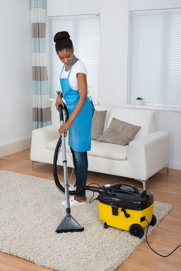 Καθαρίζοντας τάπητας γυναικών με την ηλεκτρική σκούπα στοκ εικόνα με δικαίωμα ελεύθερης χρήσης