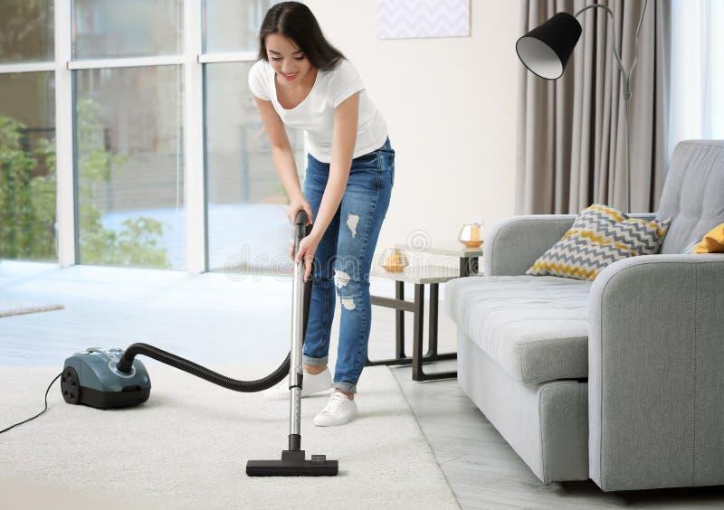 Καθαρίζοντας τάπητας γυναικών με το κενό στο δωμάτιο στοκ εικόνα