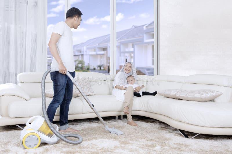 Καθαρίζοντας τάπητας νεαρών άνδρων στο σπίτι στοκ φωτογραφίες