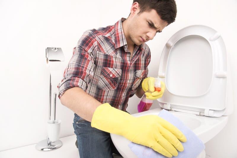 Καθαρίζοντας τουαλέτα ατόμων με τον καθαριστή ψεκασμού στοκ φωτογραφία
