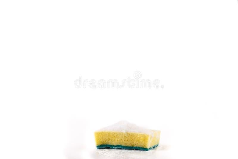 Καθαρίζοντας το μαξιλάρι για τον καθαρισμό των δοχείων με τον αφρό και το κίτρινο σφουγγάρι μαξιλάρι κουζινών, διπλάσιο στοκ εικόνες