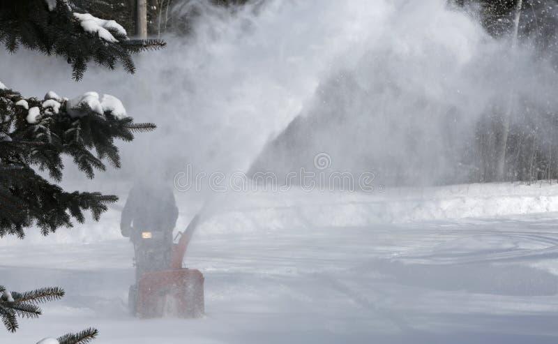 Καθαρίζοντας χιόνι ατόμων με τη φυσώντας μηχανή στοκ εικόνα με δικαίωμα ελεύθερης χρήσης