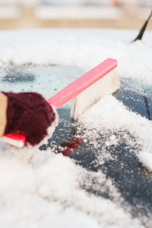 Καθαρίζοντας χιόνι γυναικών από το πίσω παράθυρο αυτοκινήτων στοκ φωτογραφία με δικαίωμα ελεύθερης χρήσης