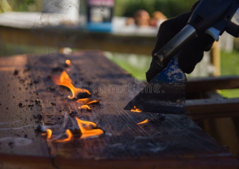 Καθαρίζοντας countertop από το παλαιό χρώμα με την πυρκαγιά ξυλουργική, αποκατάσταση των παλαιών επίπλων στοκ φωτογραφία με δικαίωμα ελεύθερης χρήσης