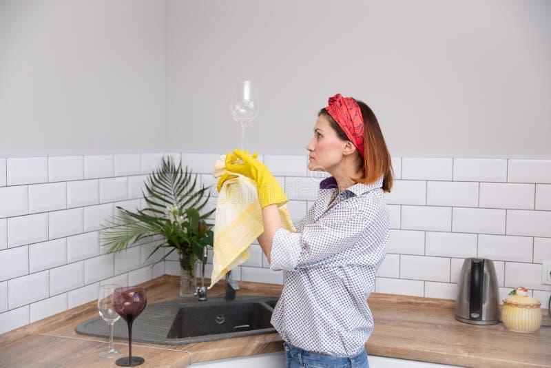 Καθαρισμός ή ruges γυαλί γυναικών στην κουζίνα στοκ εικόνες