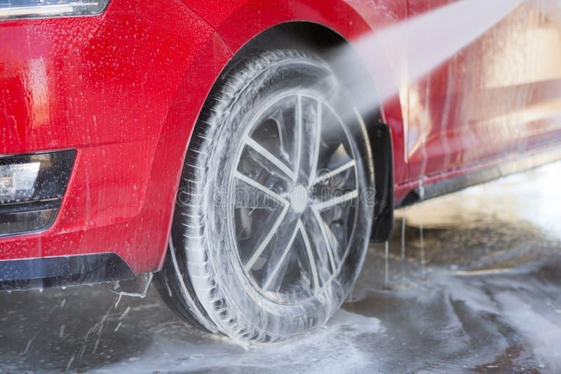 Καθαρισμός αυτοκινήτων Κόκκινο αυτοκίνητο πλυσίματος με το σαπούνι Πλύση υψηλού νερού στοκ φωτογραφία με δικαίωμα ελεύθερης χρήσης