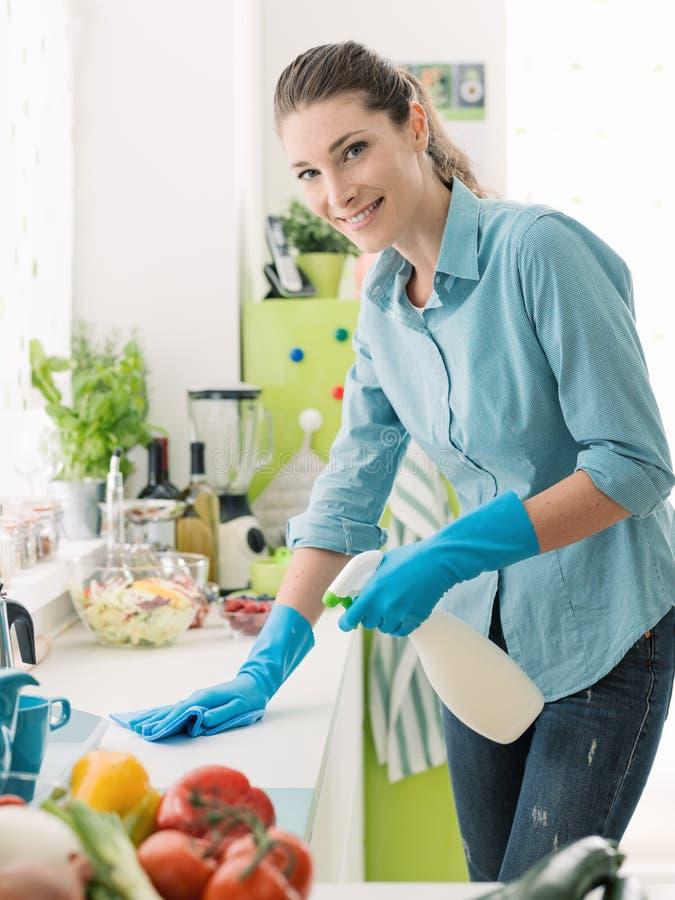Καθαρισμός γυναικών με ένα απορρυπαντικό ψεκασμού στοκ εικόνες