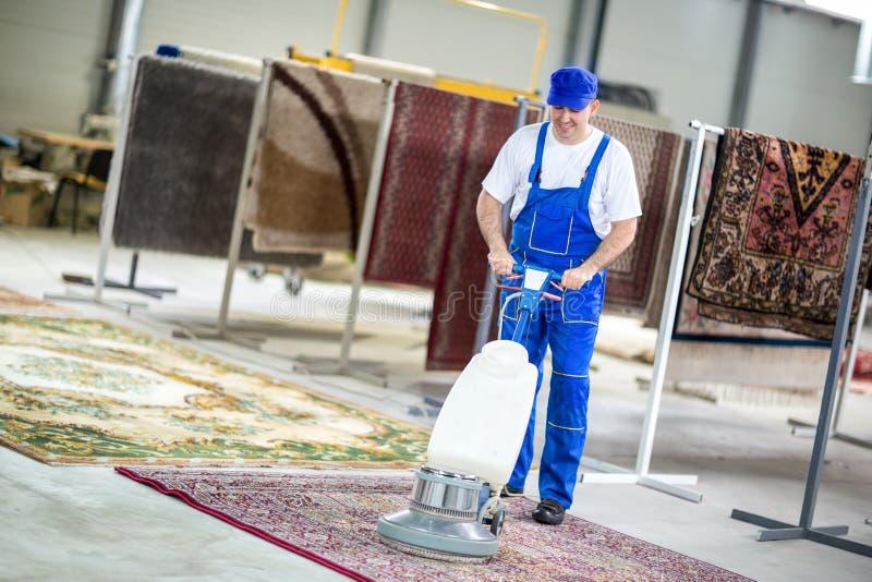 Καθαρισμός εργαζομένων με την ηλεκτρική σκούπα στοκ εικόνα
