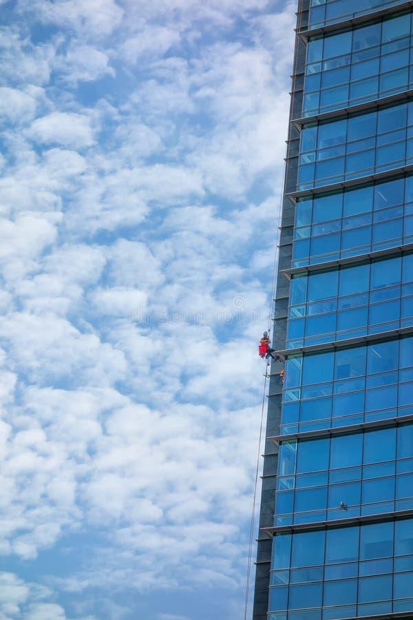 Καθαρισμός παραθύρων του ουρανοξύστη με το σχοινί Εξειδικευμένες εργασίες ris στοκ φωτογραφία με δικαίωμα ελεύθερης χρήσης