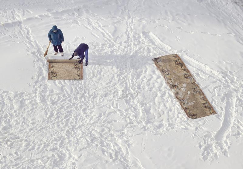 Καθαρισμός ταπήτων στα οικιακά χιονιού στοκ εικόνα