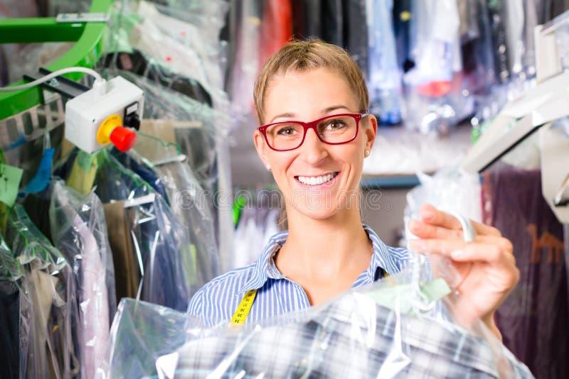 Καθαριστής στο κατάστημα πλυντηρίων που ελέγχει τα καθαρά ενδύματα στοκ εικόνες