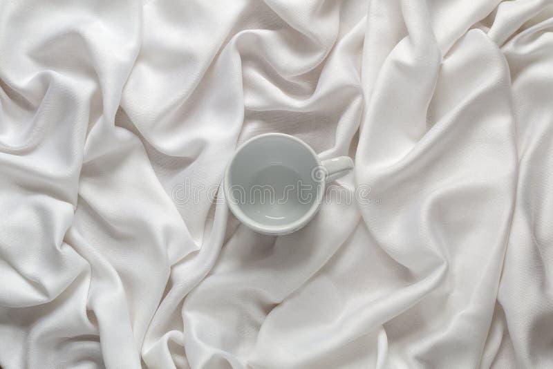 Καθαρό κεραμικό κενό φλυτζάνι καφέ στο άσπρο ύφασμα μεταξιού Τοπ όψη στοκ εικόνα