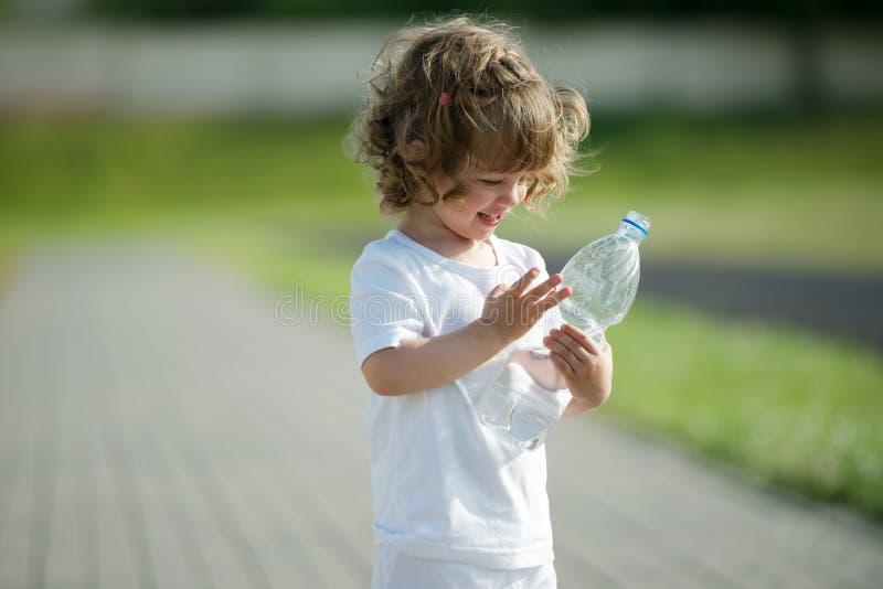 Καθαρό νερό κατανάλωσης μικρών κοριτσιών από το πλαστικό στοκ φωτογραφία με δικαίωμα ελεύθερης χρήσης