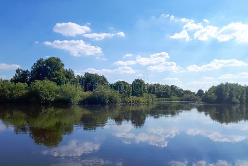 Καθαρό νερό στον ποταμό Ο καθρέφτης νερού απεικονίζει τα άσπρα σύννεφα στοκ εικόνες