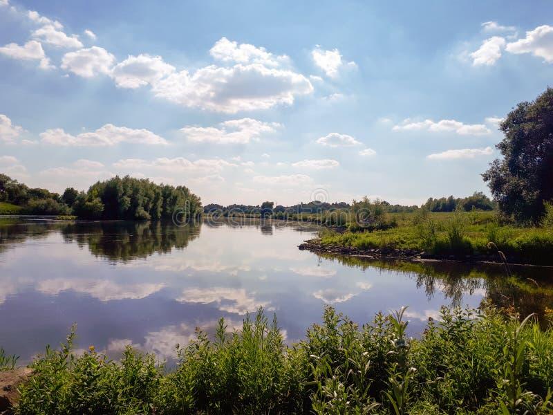 Καθαρό νερό στον ποταμό Ο καθρέφτης νερού απεικονίζει τα άσπρα σύννεφα στοκ φωτογραφία με δικαίωμα ελεύθερης χρήσης