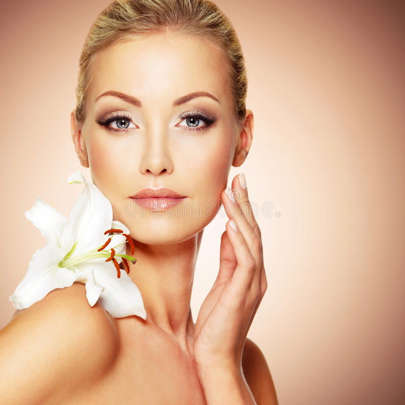 Καθαρό πρόσωπο ομορφιάς του νέου όμορφου κοριτσιού με το λουλούδι στοκ φωτογραφία