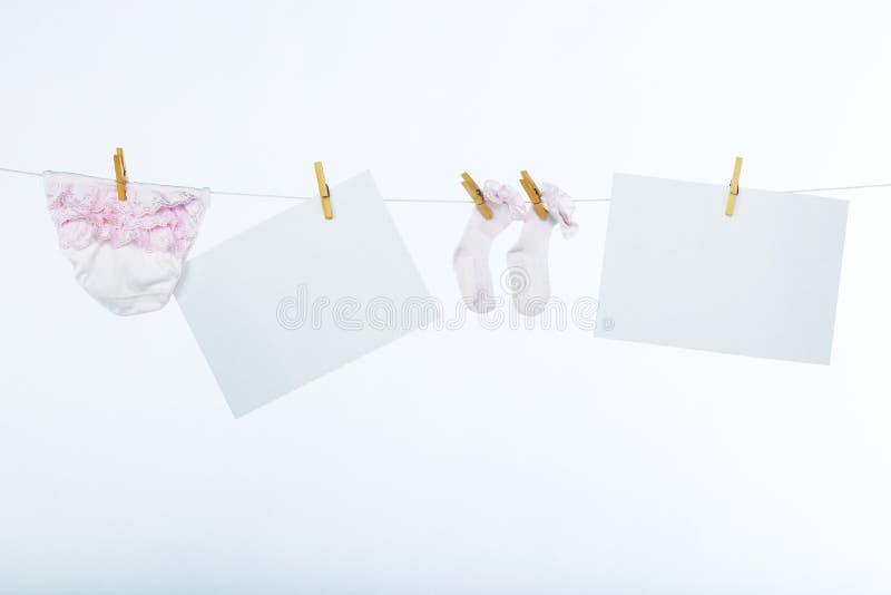 Καθαρό φύλλο δύο του εγγράφου και babyτων ενδυμάτων στοκ εικόνες