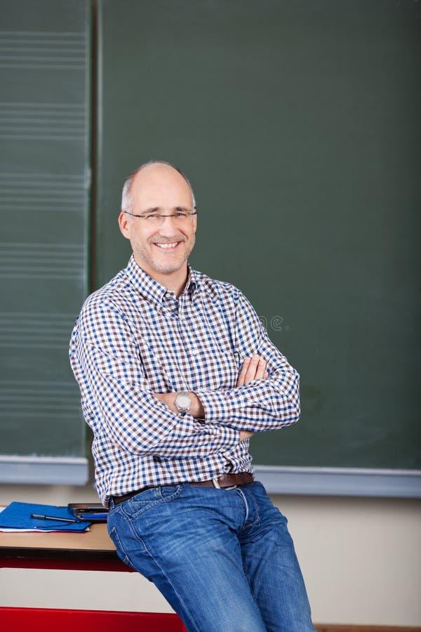 Καθηγητής με διασχισμένη την όπλα συνεδρίαση στο γραφείο στοκ φωτογραφίες
