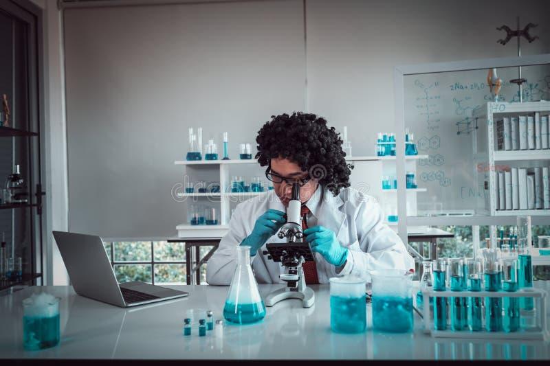 Καθηγητής που εργάζεται στο ερευνητικό κέντρο που χρησιμοποιεί ένα μικροσκόπιο φαρμακοποιοί που εργάζονται με τα μπλε υγρά στους  στοκ εικόνα με δικαίωμα ελεύθερης χρήσης