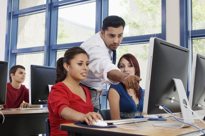 Καθηγητής Assisting Students In Class στοκ φωτογραφία