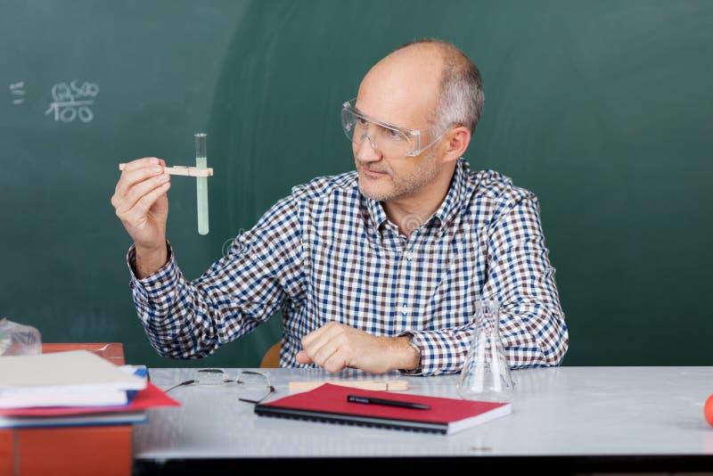 Καθηγητής Looking στο σωλήνα δοκιμής φορώντας τα προστατευτικά γυαλιά στοκ εικόνες