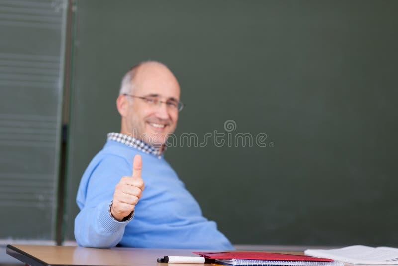 Καθηγητής Showing Thumbs Up Gesture στο γραφείο στοκ εικόνες