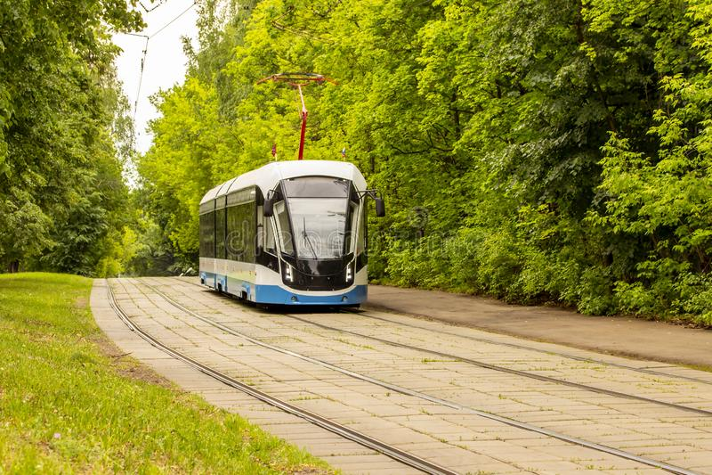 Καθιερώνοντα τη μόδα μπλε άσπρα τρεξίματα τραμ κατά μήκος των ραγών στο πάρκο Πράσινο φύλλωμα, σύγχρονο τραμ μεταφορών πόλεων οικ στοκ εικόνα