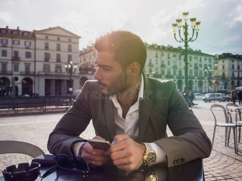 Καθιερώνον τη μόδα άτομο στον καφέ έξω από τη χρησιμοποίηση του κινητού τηλεφώνου στοκ φωτογραφίες με δικαίωμα ελεύθερης χρήσης