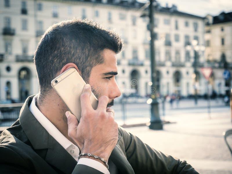 Καθιερώνον τη μόδα άτομο στον καφέ έξω από τη χρησιμοποίηση του κινητού τηλεφώνου στοκ φωτογραφία με δικαίωμα ελεύθερης χρήσης