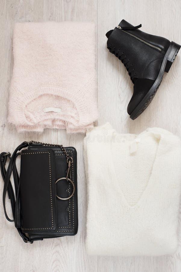 Καθιερώνον τη μόδα κολάζ ενδυμάτων μόδας γυναικών με τα πουλόβερ, τις μπότες και την τσάντα Επίπεδος βάλτε στοκ εικόνες