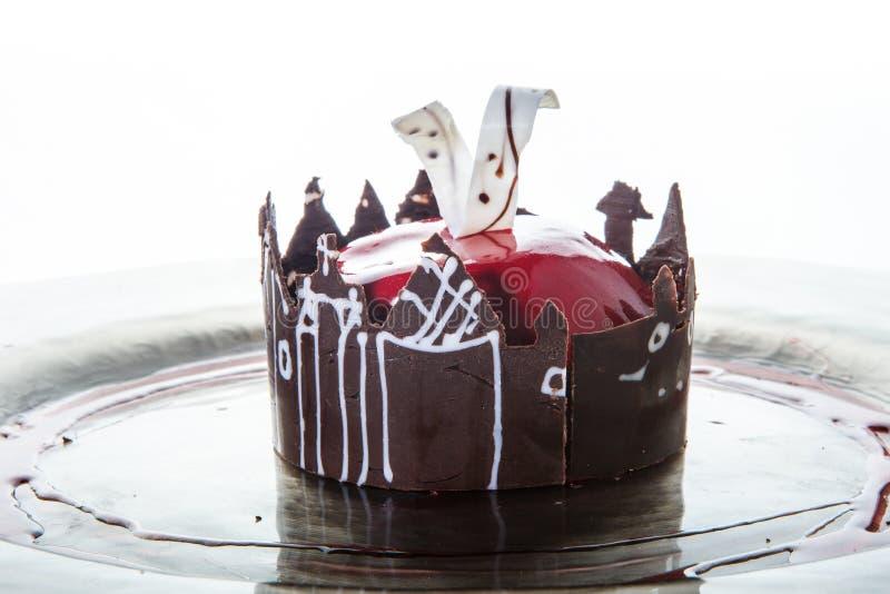 Καθιερώνον τη μόδα κόκκινο mousse κινηματογραφήσεων σε πρώτο πλάνο κέικ στη μορφή μήλων ενάντια στο λευκό στοκ φωτογραφία