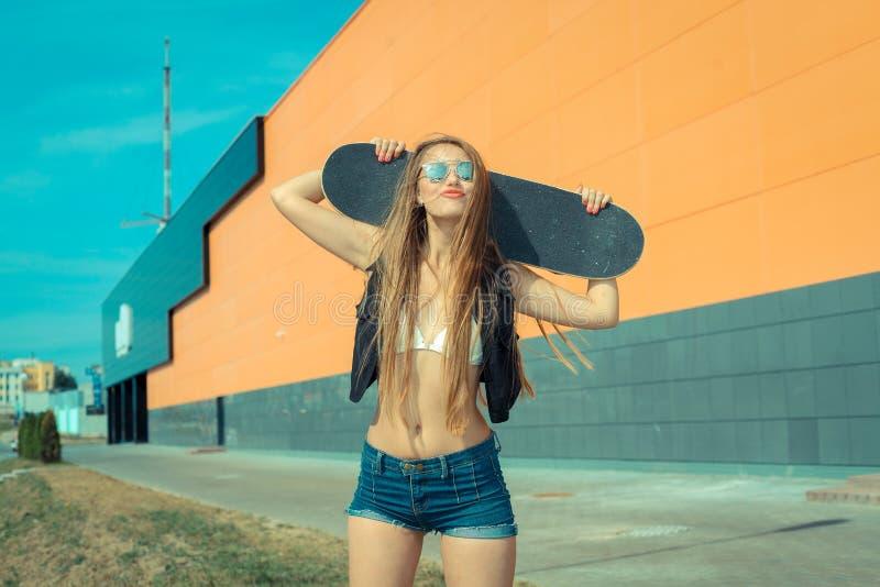 Καθιερώνον τη μόδα κορίτσι με skateboard στοκ εικόνα