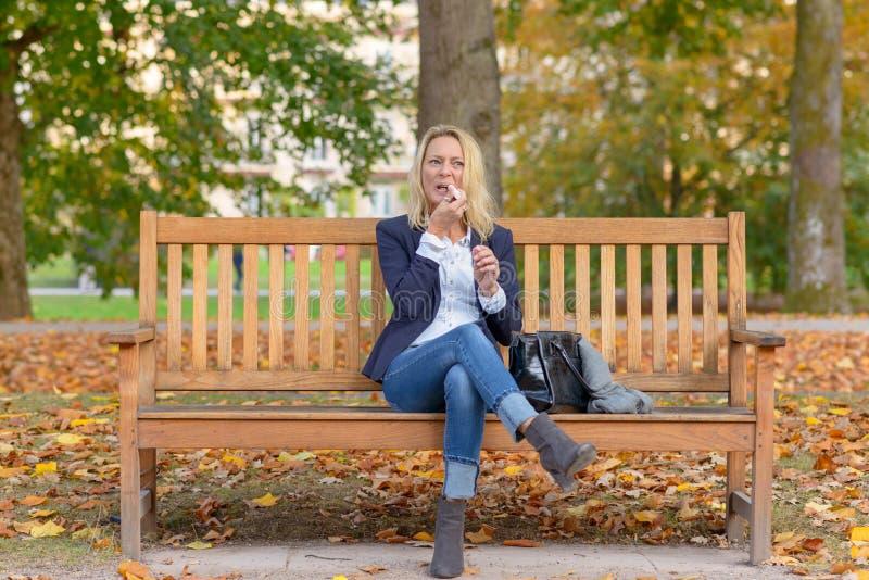 Καθιερώνουσα τη μόδα χαμογελώντας ξανθή γυναίκα που χρησιμοποιεί το κραγιόν της στοκ εικόνα με δικαίωμα ελεύθερης χρήσης