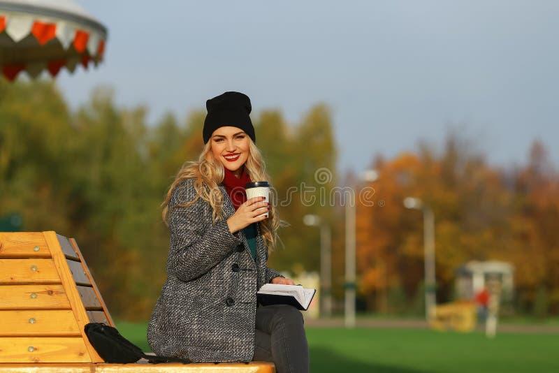 Καθιερώνουσα τη μόδα γυναίκα στη μοντέρνη συνεδρίαση παλτών στον πάγκο στο πάρκο πόλεων όμορφες χαμογελώντας νε στοκ εικόνες