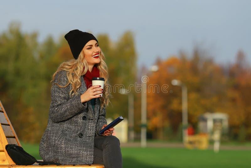 Καθιερώνουσα τη μόδα γυναίκα στη μοντέρνη συνεδρίαση παλτών στον πάγκο στο πάρκο πόλεων στοκ εικόνες