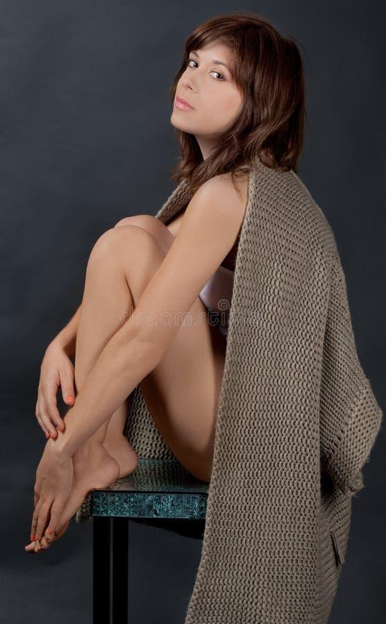 Καθισμένη γυναίκα με το πουλόβερ ντυμένο πέρα από τους ώμους στοκ εικόνες