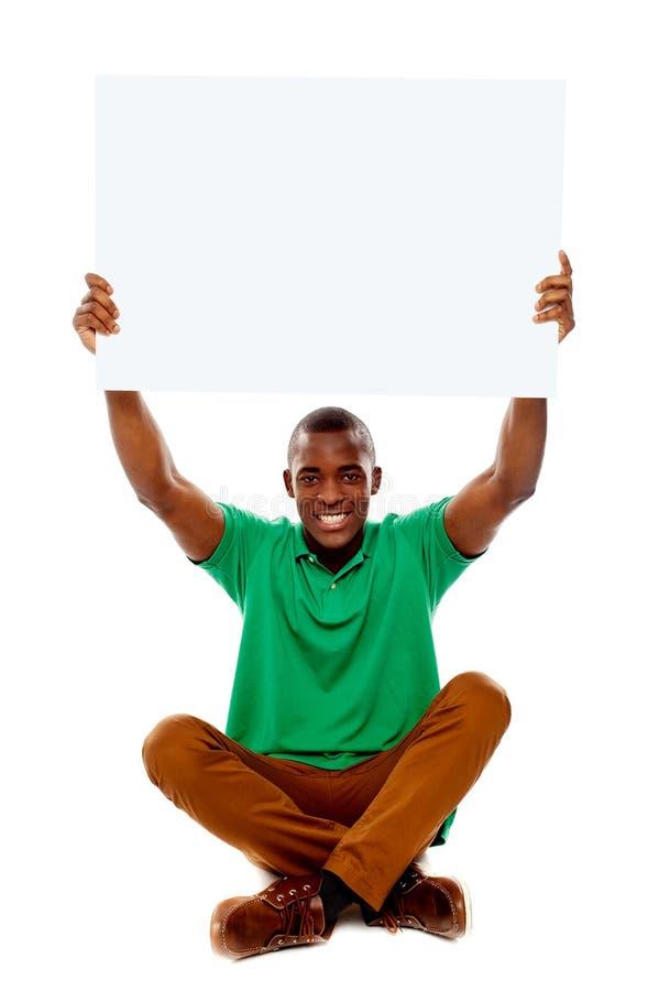 Καθισμένος νεαρός άνδρας που κρατά το άσπρο κενό έμβλημα στοκ εικόνες