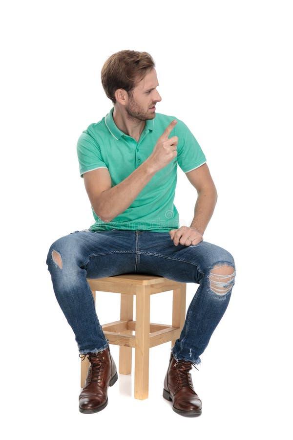 Καθισμένο εξαγριωμένο άτομο που κάνει μια παρατήρηση με το δάχτυλο στοκ εικόνες