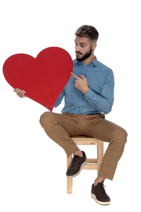 Καθισμένο περίεργο άτομο που δείχνει το δάχτυλό του μια κόκκινη καρδιά στοκ φωτογραφία με δικαίωμα ελεύθερης χρήσης