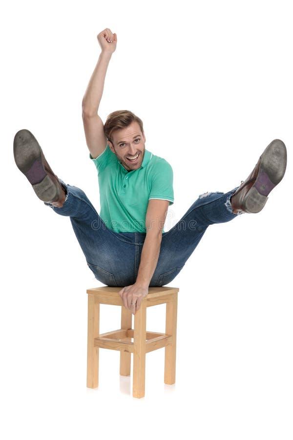 Καθισμένο σύγχρονο άτομο που ενεργεί όπως έναν κάουμποϋ που οδηγά μια καρέκλα στοκ εικόνες
