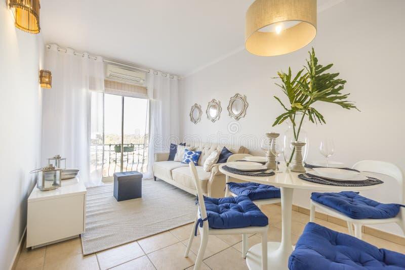 Καθιστικό με έναν να δειπνήσει πίνακα σε σύγχρονο, πολυτέλεια, φωτεινό apartm στοκ εικόνα με δικαίωμα ελεύθερης χρήσης