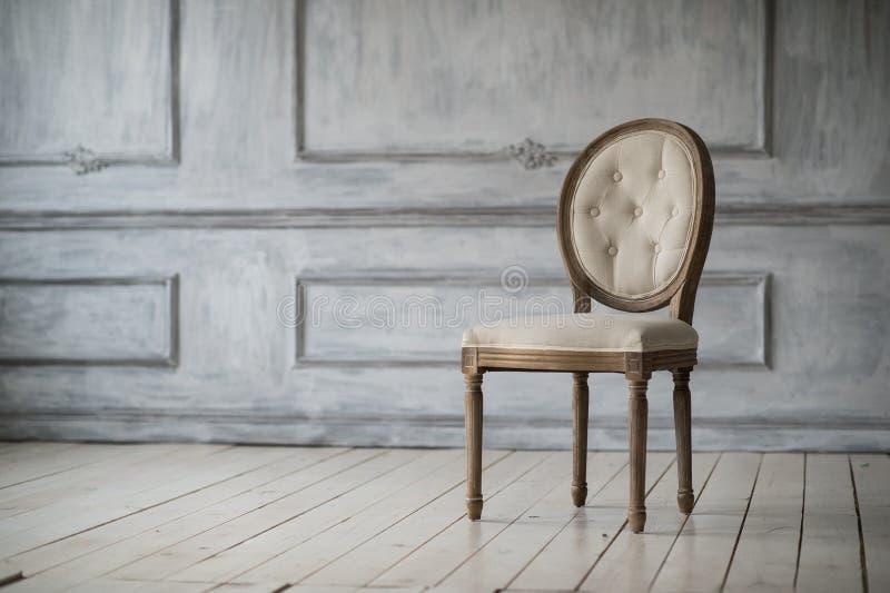 Καθιστικό με την παλαιά μοντέρνη ελαφριά καρέκλα στα άσπρα στοιχεία roccoco σχημάτων στόκων bas-ανακούφισης σχεδίου τοίχων πολυτέ στοκ φωτογραφία
