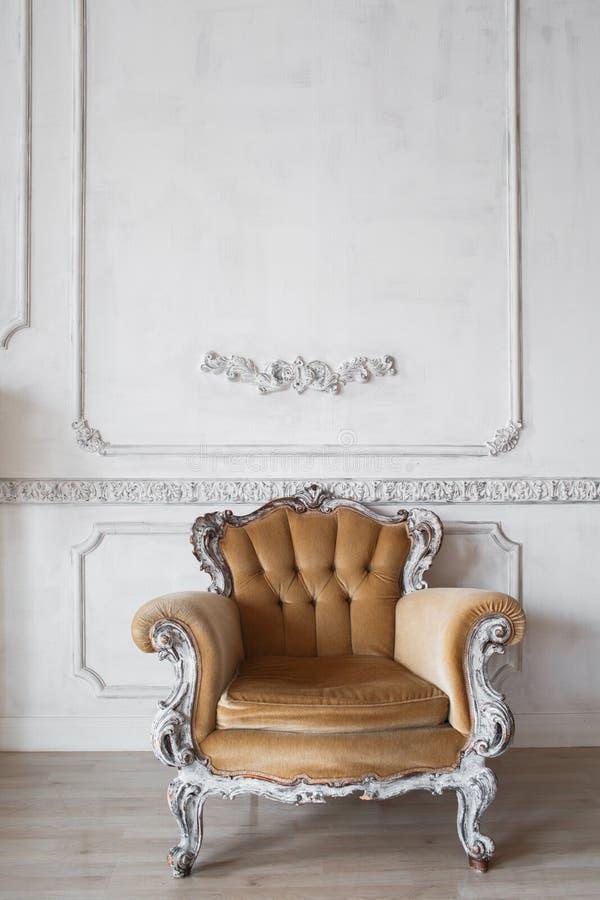 Καθιστικό με την παλαιά μοντέρνη μπεζ πολυθρόνα στα άσπρα στοιχεία roccoco σχημάτων στόκων bas-ανακούφισης σχεδίου τοίχων πολυτέλ στοκ φωτογραφίες