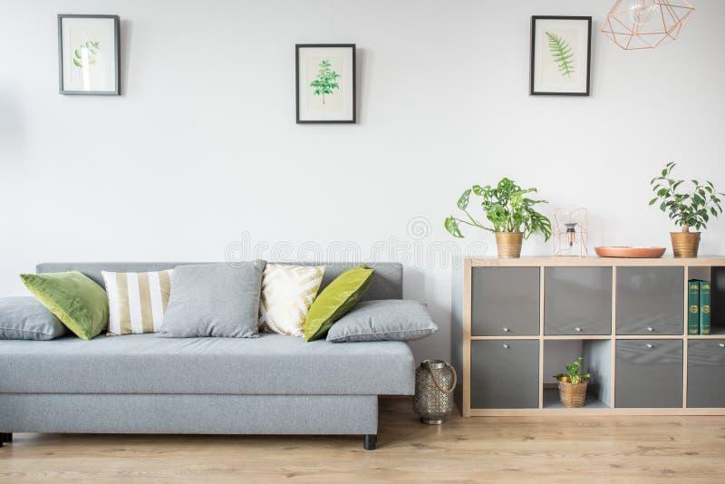 Καθιστικό με τον γκρίζο καναπέ στοκ εικόνες με δικαίωμα ελεύθερης χρήσης