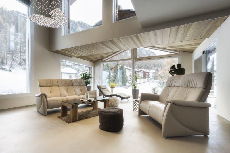 Καθιστικό του σπιτιού πολυτέλειας με τη θέα βουνού στοκ εικόνα